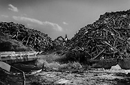 Lumber from houses destroyed by the 11 March tsunami is piled high at a permanent dump site where a crane can be seen spraying water because the wood has been catching fire due to spontaneous combustion from the heat and methane emitted during decompostion.  The spontaneous combustion adversely affects the local air quality. Yuriage, Miyagi Prefecture, Japan.