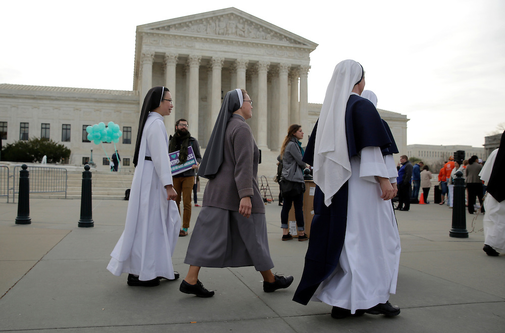 Nuns walk before Zubik v. Burwell, an appeal brought by Christian groups demanding full exemption from the requirement to provide insurance covering contraception under the Affordable Care Act, is heard by the U.S. Supreme Court in Washington March 23, 2016.      REUTERS/Joshua Roberts