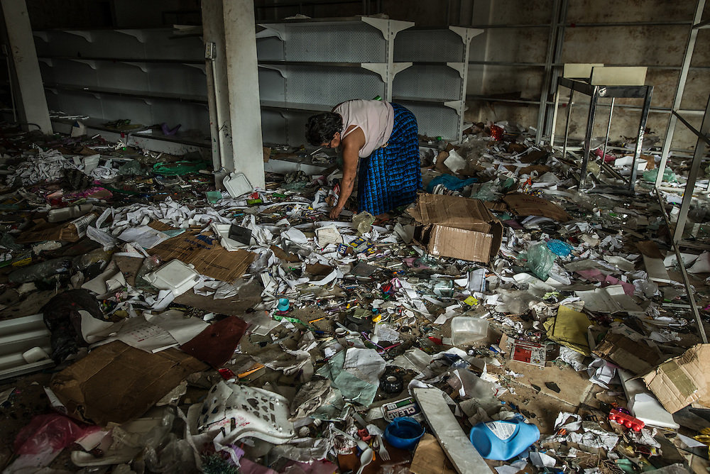 GUASIPATI, VENEZUELA - DECEMBER 17, 2016:  People loot any salvagable items from a shop destroyed and completely looted the day before - December 16, 2016 during widespread rioting in Bolivar state, in protest to President Maduro declaring the country's highest cash bill, the 100 bolivar, would be taken out of circulation and Venezuelans only had a few days to deposit them into banks.  Over 40 percent of Venezuelans do not have bank accounts.  People use only cash in Bolívar state more than other states.  Residents rioted in several cities and towns in the state, which eventually led the President to grant an extension for more time.  PHOTO: Meridith Kohut for The New York Times