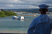 A sailor mans the rail on the USS Abraham Lincoln, as the LIncoln passes the USS Arizona Memorial.
