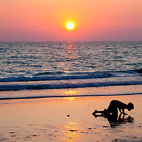A child digs for animals along St Pete Beach as the sun sets.