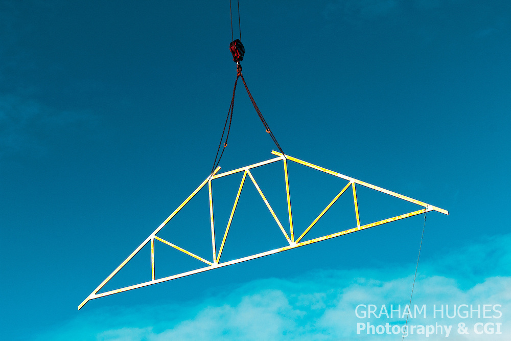 Wooden roof truss hanging from crane.