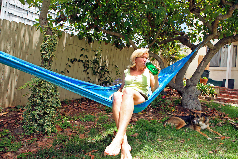 A woman enjoys a refreshing drink of water from a reusable refillable water bottle as she spends time outdoors in a hammock.