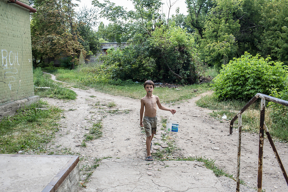 A boy who lives in the Ploshchadka neighborhood, which has been heavily bombarded in recent days, on Wednesday, July 30, 2014 in Donetsk, Ukraine.