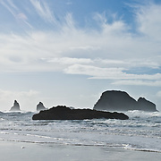 Pacific Ocean waves have eroded seastack rocks from high bluffs south of Cape Meares on the Oregon coast, USA. Clouds streak across the blue sky.