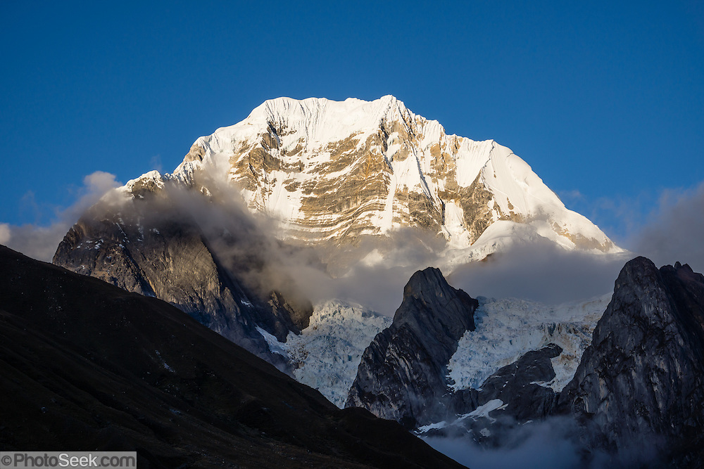 """East Face of Siula Grande (20,814 ft or 6344 m) at sunrise in the Cordillera Huayhuash, Andes Mountains, Peru, South America. Day 3 of 9 days trekking around the Cordillera Huayhuash. Siula Grande was the subject of the gripping 2003 British docudrama """"Touching the Void."""" In 1985, climbers Joe Simpson and Simon Yates scaled the treacherous West Face of Siula Grande, but after Joe broke his leg, their descent became one of the most amazing survival stories in mountaineering history. The 2003 movie is based upon Joe Simpson's harrowing book, """"Touching the Void: The True Story of One Man's Miraculous Survival."""""""