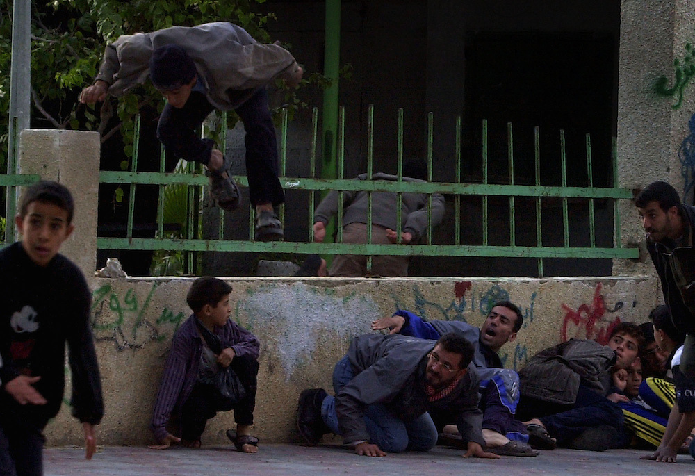 Palestinians duck, jump and flee from Palestinian police fire during a gunbattle that broke out between the Palestinian authority police and militant groups Hamas and  Islamic Jihad during a funeral procession in Jebaliya refugee camp in the northern Gaza Strip Friday Dec. 21, 2001.
