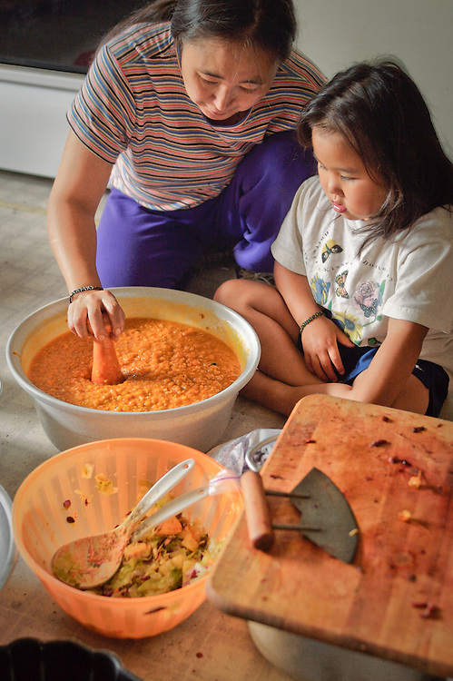 Martha Nicolai mixes berries in her kitchen with assistance from a young friend, Kwethluk, Alaska.
