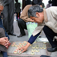 Asia, China, Beijing. Two men playing traditional Chinese board game, Banqi.