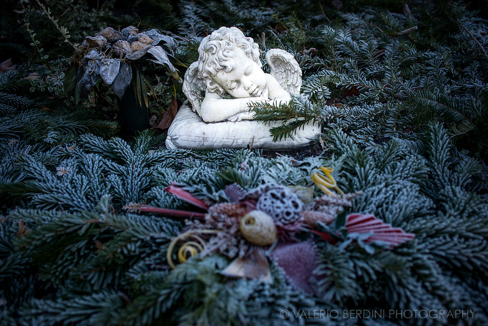 A statue of a sleeping angel on a grave as seen in a frozen morning in a cemetery in East Berlin.