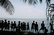 Children play on the sea wall, built to halt erosion of the land by the waves, Puil Island, Carteret Atoll, Papua New Guinea, on Sunday, Dec. 10, 2006. Rising sea levels have eroded much of the coastlines of the low lying Carteret islands (situated 80km from Bougainville island, in the South Pacific), and waves have crashed over the islands flooding and destroying what little crop gardens the islanders have. Food is in short supply, banana and swamp taro crops are failing due to the salt contamination of the land, and the islanders live on a meagre one meal per day diet of fish and coconut. There is talk by the Autonomous Region of Bougainville government to relocate the Carteret Islanders to Bougainville island, but this plan is stalled due to a lack of finances, resources, land and coordination.