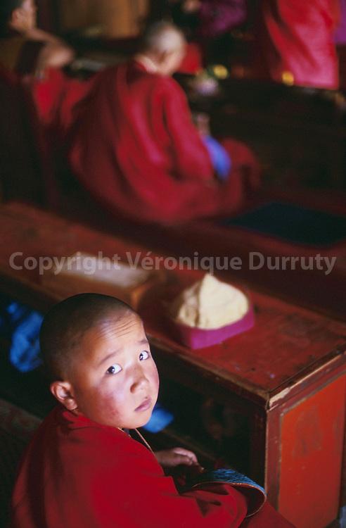 Little buddhist monk during a ceremony, Shank monastery, Mongolia // MONASTERE SHANKH, OVORKHANGAI, MONGOLIE Petit moine bouddhiste tibétain pendant une cérémonie. Le bouddhisme lamaïste est avec le chamanisme, la principale religion de Mongolie. Cette religion connait un fort regain d'intérêt depuis la libéralisation des années 1990. Rappelons que le dalaï-lama de Lhassa au Tibet a souvent été originaire de la Mongolie, car le Tibet a longtemps fait partie de la Mongolie.