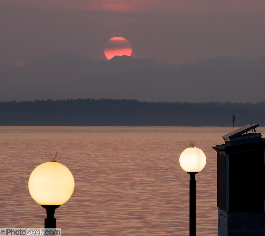The sun sets like an orange ball over the Olympic Mountains and Puget Sound, seen from a globe-lit waterfront in downtown Seattle, Washington. Spikes keep birds off the lighting spheres.