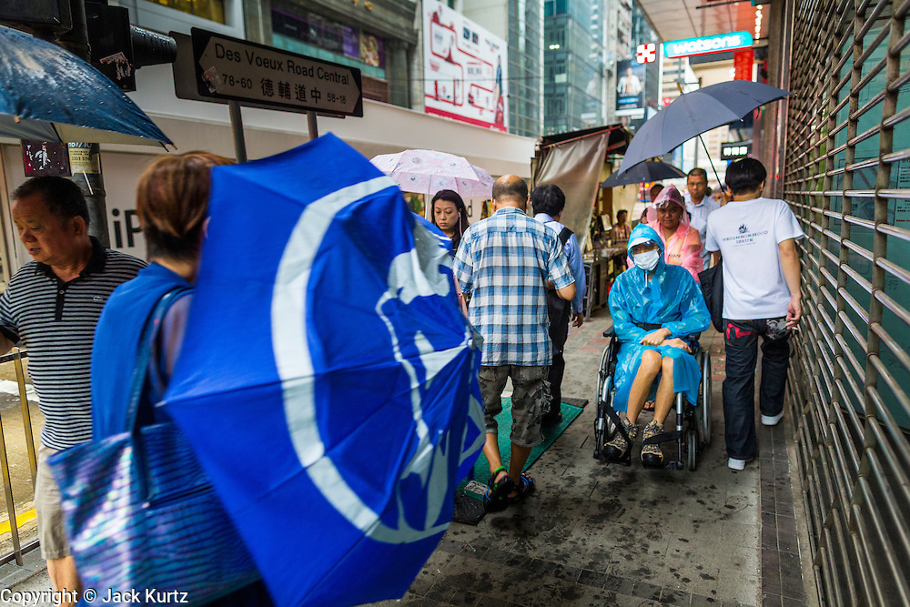 13 AUGUST 2013 - HONG KONG:  People on Des Voeux Road in Hong Kong during Typhoon Utor. Typhoon Utor (known in the Philippines as Typhoon Labuyo) is an active tropical cyclone located over the South China Sea. The eleventh named storm and second typhoon of the 2013 typhoon season, Utor formed from a tropical depression on August 8. The depression was upgraded to Tropical Storm Utor the following day, and to typhoon intensity just a few hours afterwards. The Philippines, which bore the brunt of the storm, reported 1 dead in a mudslide and 23 fishermen missing at sea. The storm brushed by Hong Kong bringing several millimeters of rain and moderate winds to the island but causing no reported damage or injuries. It is expected to make landfall in China.  PHOTO BY JACK KURTZ
