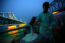 A Chinese street vendor makes traditional North Korean glutinous rice cakes  beside the Sino-Korean Friendship Bridge (L) connecting Sinuiju, North Korea, and the Yalu River Bridge (R) along the Yalu River in the Chinese city of Dandong, Liaoning Province, China on 05 April 2013. North Korea recently moved a ballistic missile to its east coast in a seeming show of strength or in readiness for a launch, Yonhap News Agency reported 04 April. Tensions have risen as Pyongyang's third nuclear test in February led to a tightening of international sanctions against it, with its closest ally China calling for calm on all sides.