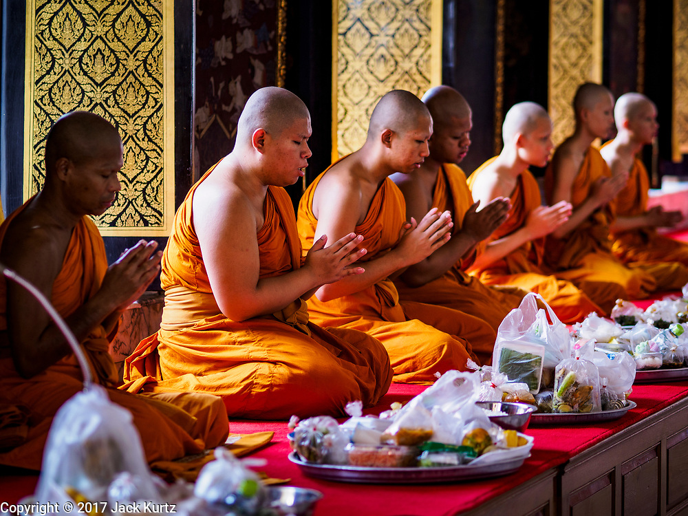 "11 APRIL 2017 - BANGKOK, THAILAND: Buddhist monks pray in Wat Chana Songkhram during a Songkran merit making service. Songkran is the traditional Thai Lunar New Year. It is celebrated, under different names, in Thailand, Myanmar, Laos, Cambodia and some parts of Vietnam and China. In most places the holiday is marked by water throwing and water fights and it is sometimes called the ""water festival."" This year's Songkran celebration in Thailand will be more subdued than usual because Thais are still mourning the October 2016 death of their revered Late King, Bhumibol Adulyadej. Songkran is officially a three day holiday, April 13-15, but is frequently celebrated for a full week. Thais start traveling back to their home provinces over the weekend; busses and trains going out of town have been packed.     PHOTO BY JACK KURTZ"