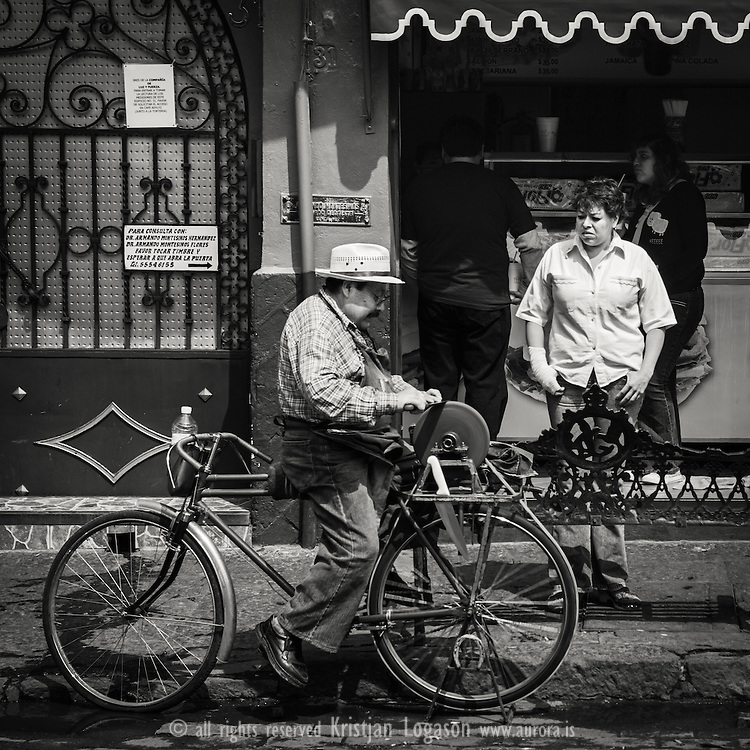 Man using his bicycle to turn the whetstone sharpening knife at a market square in Coyoacán, Mexico city while a woman with bandages stands by waiting
