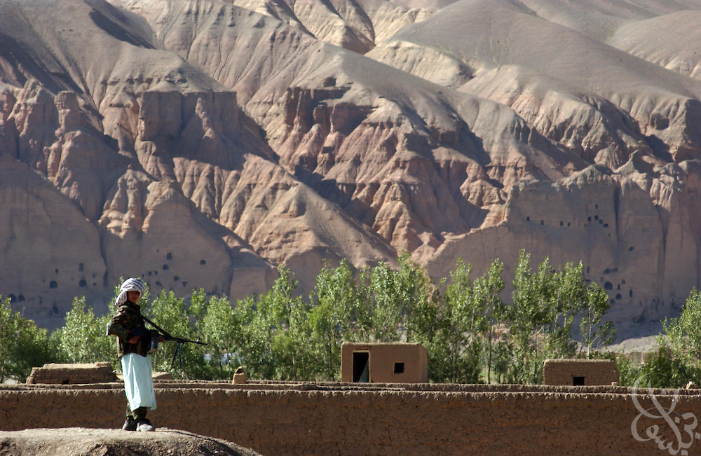 An armed Afghan national militiaman secures an airstrip for coalition forces June 17, 2002 in Bamiyan, Afghanistan. Bamiyan was famed for the giant Buddha statues that were carved centuries ago in the cliffs seen behind the gunman, before they were destroyed by taliban fighters in 1991.