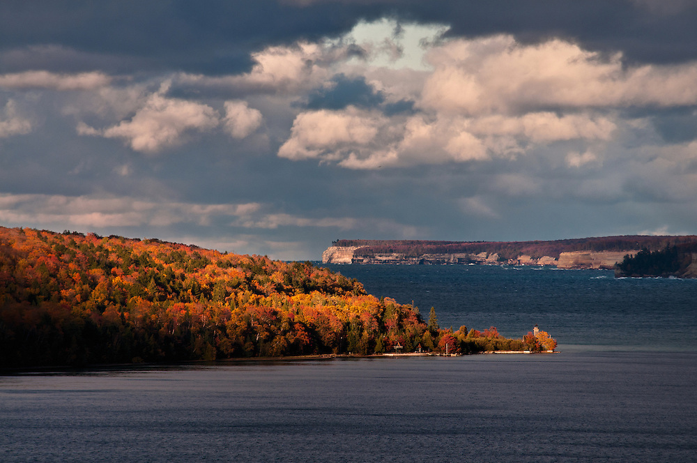 The clouds rolling back to reveal the fall colors of Grand Island, Pictured Rocks in the background.<br /> Munising, Michigan's Upper Peninsula