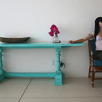 Woman smiling and sitting next to turquoise table with bugambilia flowers.<br /> Photo shooting took place in a modern, minimalistically decorated beachfront home in exotic small town of Los Barriles, Baja California Sur, Mexico. <br /> Home decoration is comprised of different color selections, each used with careful combination of details and accompanying furniture, plants and other decorative elements. Prevailing colors are white, red and striking turquoise blue.<br /> Here we are showing photographs from 2 parts of this home; guest bedroom and inner patio, where magnificent red wall with agavas welcomes you upon arrival. And if you are lucky enough to get an invite to stay in the house over night, you will enjoy a beautiful bedroom, with minimal decoration, but very attractive, relaxed and Mexican, but in a contemporary way.