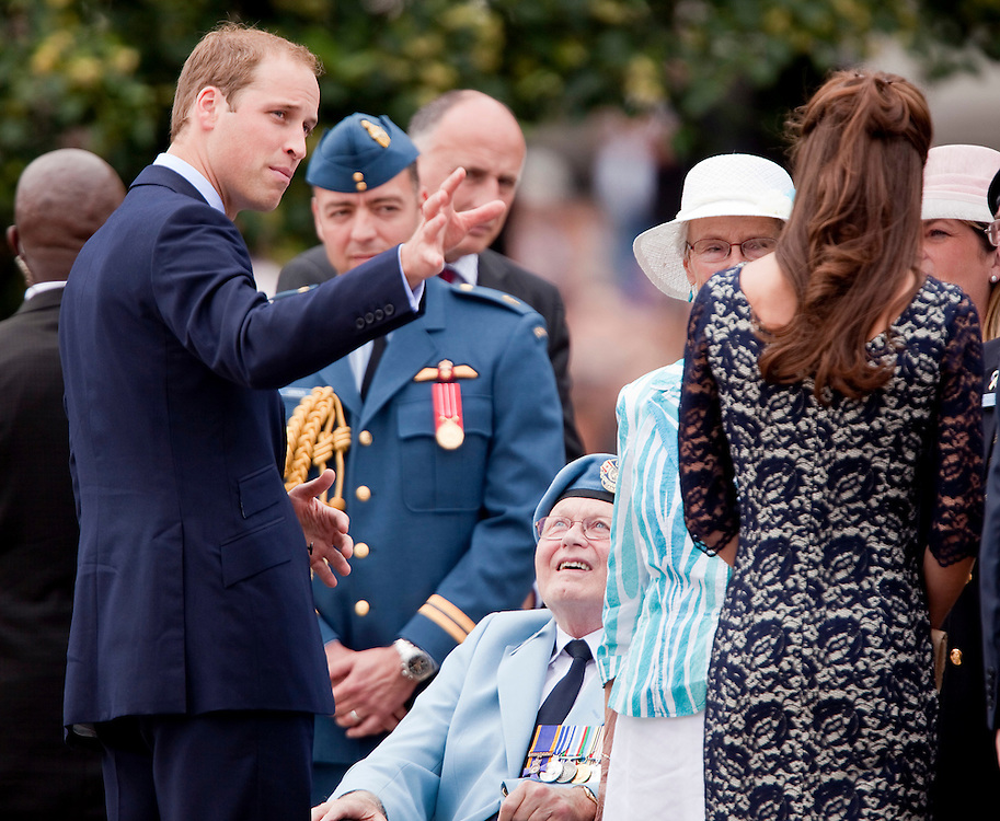 Britain's Prince William and his wife Catherine the Duchess of Cambridge speak to veterans during a ceremony at the National War Memorial in Ottawa, Canada,  June 30, 2011, the first stop on their nine-day tour of Canada, kicking off their first official foreign trip as husband and wife.<br /> AFP PHOTO/GEOFF ROBINS