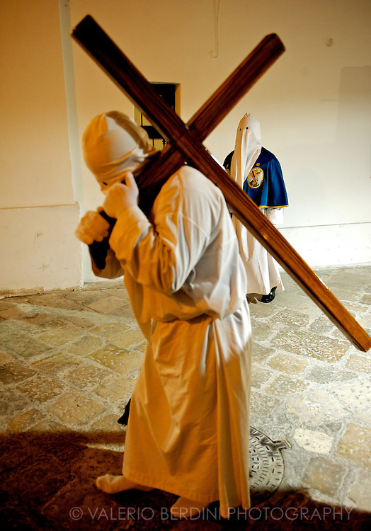 A penitent walks the path bearing the cross