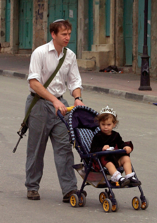A Jewish settler carrying an M-16 automatic rifle pushes his daughter in a stroller during their morning walk on the Sabbath in the divided West Bank city of Hebron Saturday, March 31, 2001. The central area of Hebron remains under strict closure as the city has been especially tense since the killing of an Israeli baby there by Palestinian fire earlier in the week.