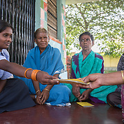 CAPTION: When her mother is unable to attend, Padma stands in for her at their local self-help group (SHG) meetings. This is made up of people from their locality who either live with a disability or have a close family member who does. In their case, Padma's brother Shesh Naik lives with multiple disabilities, including cerebral palsy. LOCATION: Amchawadi (village), Haradanahalli (hobli), Chamrajnagar (district), Karnataka (state), India. INDIVIDUAL(S) PHOTOGRAPHED: From left to right: Padma, Sakamma, Chikkatayamma and unknown.