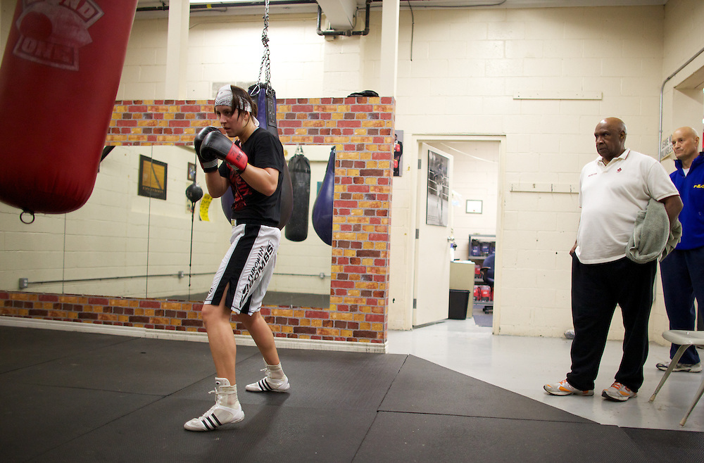 Windsor, Ontario ---10-05-06--- World Welterweight Champion, Mary Spencer hits a heavy bag as coach Charlie Stewart  looks on during a training session at the Windsor Amateur Boxing Club in Windsor, Ontario, May 6, 2010.<br /> GEOFF ROBINS The Globe and Mail