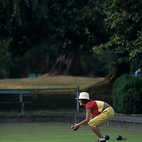 Canada, British Columbia, Vancouver, (MR) Asian-Canadian woman plays lawns bowls at club in Stanley Park