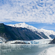 The tidewater Cascade and Barry Glaciers pour from the steep and glaciated Chugach Mountains into Barry Arm of Prince William Sound, Alaska, USA. Prince William Sound is surrounded by Chugach National Forest (the second largest national forest in the USA). Tour spectacular Prince William Sound by commercial boat from Whittier, which sits strategically on Kenai Peninsula at the head of Passage Canal. Whittier is a port for the Alaska Marine Highway System, a ferry service which operates along the south-central coast, eastern Aleutian Islands, and the Inside Passage of Alaska and British Columbia, Canada. Cruise ships stop at the port of Whittier for passenger connections to Anchorage (by road 60 miles) and to the interior of Alaska via highway and rail (the Denali Express). Known by locals as the Whittier tunnel or the Portage tunnel, the Anton Anderson Memorial Tunnel links Whittier via Portage Glacier Highway to the Seward Highway and Anchorage. At 13,300 feet long (4050 m), it is the longest combined rail and highway tunnel in North America. Whittier was severely damaged by tsunamis triggered by the 1964 Good Friday Earthquake, when thirteen people died from waves reaching 43 feet high (13 meters). Panorama stitched from 4 overlapping photos.