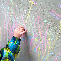 Toddler writing on a concrete wall with chalk