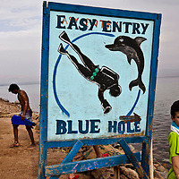 """A diver walks past a sign for the Blue Hole outside of Dahab, Egypt. The Blue Hole is notorious for the number of diving fatalities which have occurred there, earning it the sobriquet """"World's Most Dangerous Dive Site"""" and the nickname """"Diver's Cemetery"""". The site is signposted by a sign that says """"Blue hole: Easy entry"""". Accidents are frequently caused when divers attempt to find the tunnel through the reef (known as """"The Arch"""") connecting the Blue Hole and open water at about 52 m depth. According to dive experts roughly 10 people die each year. April 2012."""