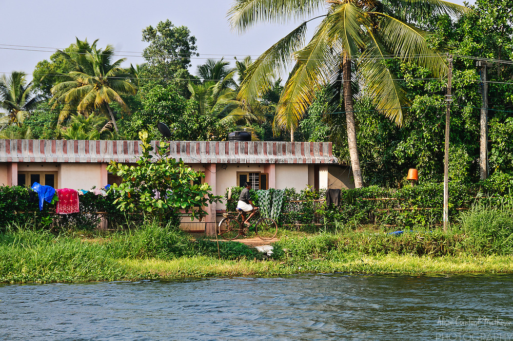 A my cycles beside a canal in the Kerala backwaters