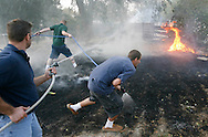 "Neighbors battle a brush fire with garden hoses after a Sept. 3 wind storm downed a power line into the field in the bench neighborhood. Craig Burden, who owns the house next to the charred field, came home from McCall a few days later to find a large hole burned into his trampoline and his garden hose missing..""At least they saved the house from going up,"" he said."