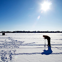 Drilling ice fishing holes through the ice  on Lake Monona Bay in Madison, Wisconsin.