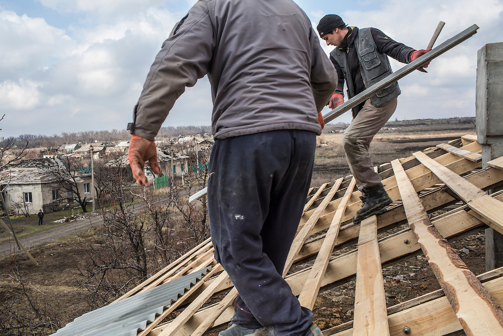 Men repair the roof of an apartment building that was destroyed, like practically every other building in town, by shelling during fighting last winter on Sunday, March 27, 2016 in Nikishyne, Ukraine.