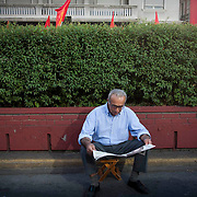 A supporter of the Greek communist party (KKE) reads the parties local newspaper (Rizospasti) at the speech of Aleka Papariga in Athens, Greece. Image © Angelos Giotopoulos/Falcon Photo Agency
