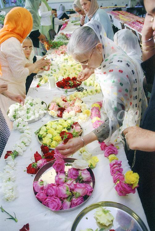 Elderly Asian women making garlands for the Baisakhi festival,