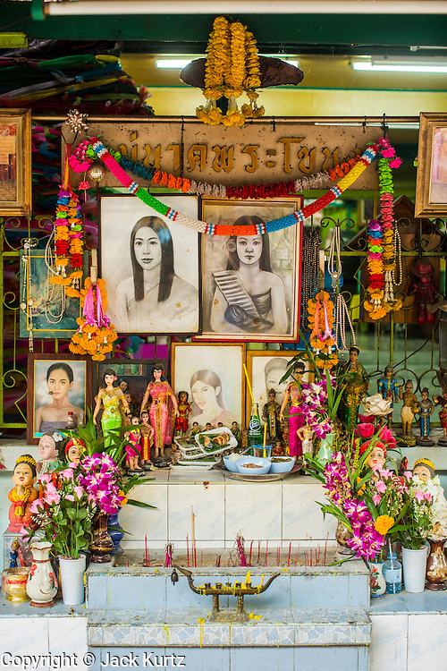 "04 JANUARY 2012 - BANGKOK, THAILAND: The ""Mae Nak"" Shrine at Wat Mahabut in eastern Bangkok.  ""Mae Nak"" is one of the most famous of all Thai ghosts. Legend has it that she died while pregnant when her husband was away serving as a soldier in the Siamese army. People come from across Bangkok to pray at the shrine, seek good fortune and lucky lottery numbers. The temple was built in 1762 and predates the founding of the city of Bangkok. Just a few minutes from downtown Bangkok, the neighborhoods around Wat Mahabut are interlaced with canals and still resemble the Bangkok of 60 years ago. Wat Mahabut is a large temple off Sukhumvit Soi 77. The temple is the site of many shrines to Thai ghosts. Many fortune tellers also work on the temple's grounds.    PHOTO BY JACK KURTZ"