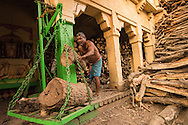 Man cutting wood for funeral pyres to burn cremations on the Ganges, Varanassi, India