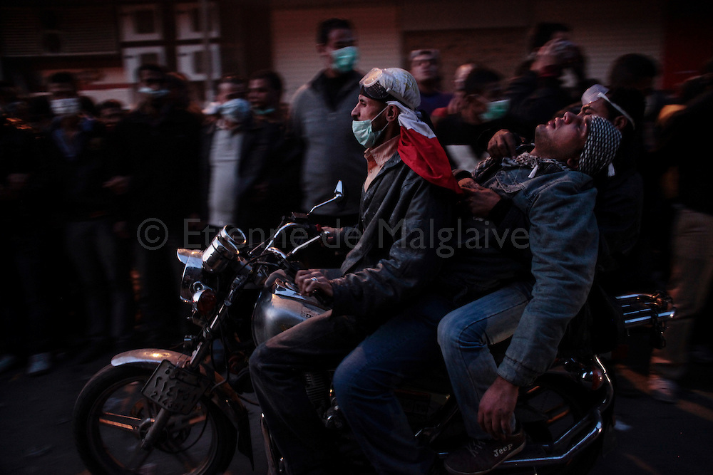 An injured protester is swiftly evacuated  by motorbike for treatment during clashes with riot police on Mohamed Mahmoud street near Tahrir Square on November 22, 2011 in Cairo, Egypt.