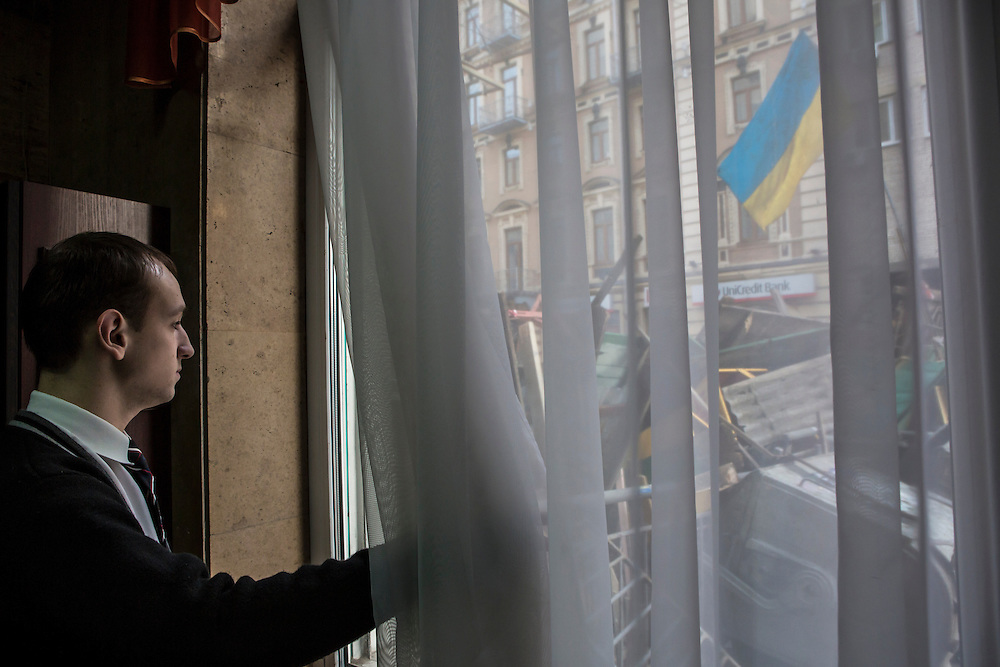 KIEV, UKRAINE - FEBRUARY 19: A hotel clerk looks out the lobby window at a barricade that was constructed on an adjacent street overnight near the perimeter of Independence Square, known as Maidan, on February 19, 2014 in Kiev, Ukraine. After several weeks of calm, violence has again flared between police and anti-government protesters, who are calling for the ouster of President Viktor Yanukovych over corruption and an abandoned trade agreement with the European Union. (Photo by Brendan Hoffman/Getty Images) *** Local Caption ***