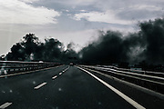 Thick toxic black smoke drifts across a major highway in Giugliano. Tumors have increased by 47 percent among men in this province of Naples within the past two decades.