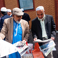 London, UK - 20 July 2012: two men read newspapers outside of the East London Mosque as London's Muslim community celebrates the first day of Ramadan.