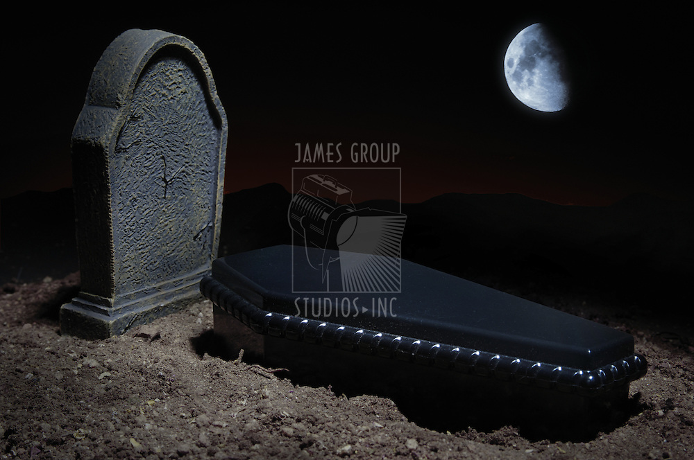 Grave site at night time with casket, headstone and moon in the sky