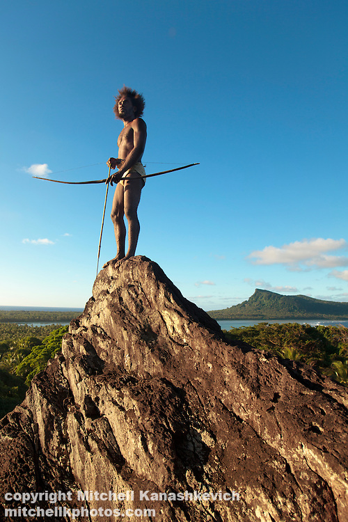 Traditional Ni Vanuatu man scans his surroundings with a bow and arrow from the Rock of Rah, Rah Lava Island, Torba Province, Vanuatu