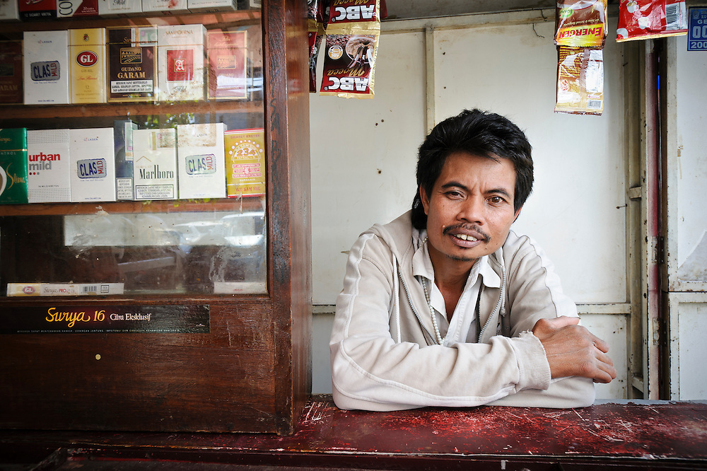 Bapak Agus at his kiosk outside the Jongaya leprosy settlement, Makassar, Sulawesi, Indonesia. Bapak Agus was born in 1968.  He first found out that he was infected with leprosy when he was 18 years old but received no treatment for two years.  He now has problems with his hands and had his foot amputated several years ago.  He met his current wife, Ibu Hamriani, at the Daya leprosy hospital and they married in 1999.  He has two children - Samsida, 21, from a previous marriage, and Nurlina, 11, from his marriage with Ibu Hamriani.  None of his children have leprosy.  Bapak Agus runs a small kiosk selling cigarettes, coffee and phone credit outside of Jongaya, and also helps teenagers from the settlement to find work away from the settlement.