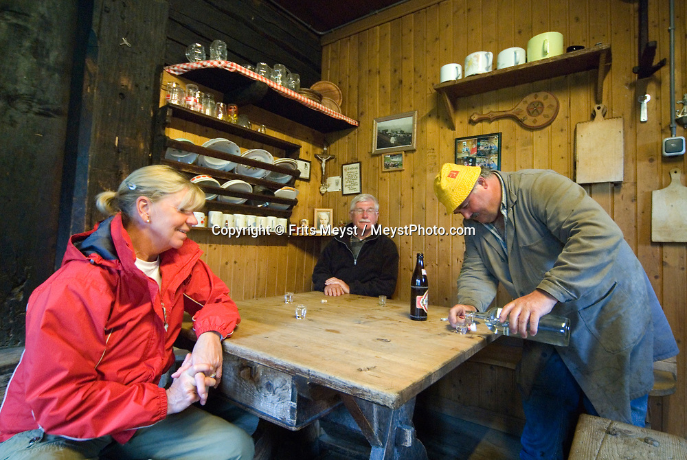 Duerrstein Alm, Stuhlfelden, National Park Hohe Tauern, Salzburgerland, Austria, May 2009. Drinking schnapps and beer with the hospitable farmers on the alm. The Duerrstein Alm is run by Theresia Bacher who grew up in one of the 3 huts on the alpine pasture. Photo by Frits Meyst/Adventure4ever.com