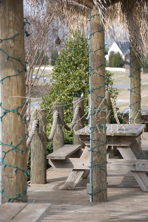 An outdoor dining area including picnic tables on a deck with rope railings and Christmas lights on vertical poles.